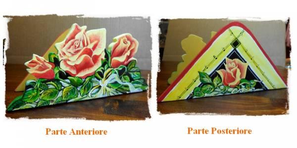 porta tovaglioli che raffigura un mazzo di rose, adagiate su un velo bianco, intagliato in legno dipinto a mano, a partire da un disegno realizzato ed ideato da Paolo Matteoni